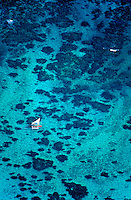 A sailing outrigger canoe glides over the turquois blue waters and coral reefs of windward Oahu.