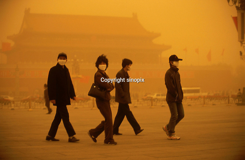 Tourists wear face masks in Tiananmen Square in Beijing. When dust storms strike the capital, they turn the sky an amber color and reduce visibility to around a hundred meters. Extensive deforestation and desertification in northern China have fueled the dust storms. Nearly one million tons of Gobi Desert sand blows into Beijing each year. ..LOU / SINOPIX.