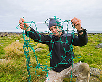 """Researcher John Gibbens holds trawl netting removed from neck of entangled juvenile northern fur seal, Callorhinus ursinus, St Paul Island, Alaska. Model Release available. Any reproduction must include the caption """"photographed under NMFS permit 14329"""""""