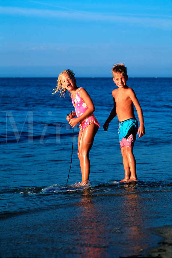Two smiling young children enjoying the expansive beach and water of Cape Cod's National Seashore. Truro, Massachusetts.
