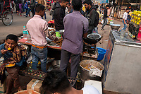 People eat at a food vendor's stall in the street market on Meena Bazar in the Chadni Chowk area of Delhi, India, on Tue., Dec. 11, 2018.