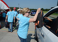 Becky Carter, a church member at Round Mountain Community Church, hands food and a backpack full of school supplies Saturday, July 31, 2021, to a resident during the church's annual Back2School Backpack Giveaway at Elkins High School. The annual effort began with about 50 backpacks and has grown to serve 600 students. Visit nwaonline.com/210801Daily/ for today's photo gallery.<br /> (NWA Democrat-Gazette/Andy Shupe)