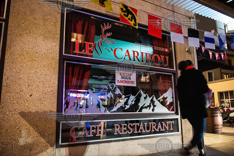 A protest sign in the window of a closed restaurant reads 'The State is sacrificing us'. The restaurant, in Geneva's multi-cultural Paquis district, has been closed to eat-in customers during the second wave of the COVID-19 pandemic. The flags represent the different Swiss cantons.