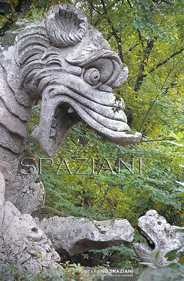 "The Dragon,..The legendary beast by excellence the winged Dragon, while it fights, not against man, but other beasts. The Park of the Monsters of Bomarzo.The Park of the Monsters  also named Sacred Wood is a Renaissance monumental complex located in Bomarzo, in the province of Viterbo, in northern Lazio, Italy.25 jun 2012..In the region of Lazio, the marvellous land of the Etruscans, the Romans and the Middle Ages, lies the village of Bomarzo which shares all the glory of the region's illustrious history and possesses an historical site which is the only one of its kind in the world: ""The Villa Of Marvels"". In the gardens of other villas in Lazio you will find certain similirities, but the prototype of all these gardens remains the ""Sacred Wood of Bomarzo"", that popular fancy rebaptized as Monster's Park. Prince Pier Francesco Orsini, known as Vicino, wanted such a park ""only to ease the heart"". It was designed and laid out by the great architect, Pirro Ligorio, who was summoned to work at Saint Peter's in Vaticano after the death of Michelangelo. Without either Prince Orsini or Ligorio ever realizing it, a timeless masterpiece was born. When you visit this park you will go from surprise to surprise as animals and figures in stone suddenly appear: the Elephant that is about to kill a Warrior, the fighting Dragons, the Ogre in whose mouth you could pic-nic, Sleeping Beauty, Hercules tearing Cacus apart, Bears in ambush, animals with three heads, Neptune presiding figures, and finally a globe of the world balanced on the head of an Orc with a model of the Orsini Castle on top representing the power of his family. These sculptures carred out of massive boulders in situ, appearing to rise up out of the very ground as if by magic. It all goes back to the 16th Century (1552), the period which saw the development of an ideal of life between Prince and Courtier. This wood has inspired many important artists and poets of the time such as Annibal Caro, Bitussi and Cardinal Ma"