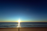 Solitary person walking on the beach at sunrise, Nauset Beach, Cape Cod, Massachusetts, USA