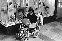 England. Greater Manchester. Salford. Hairdresser salon's   window in a commercial center. A lonely old woman is seated on a wheelchair and smoke a cigarette. Women living in poverty. Salford is a city in the Metropolitan Borough of Salford in Greater Manchester. North West England is one of nine official regions of England. © 1990 Didier Ruef
