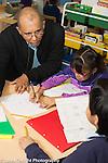 Afterschool homework help program for Headstart graduates Grades K-3 male teacher working with third grade students
