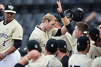 Jonathan Pryor (center) is congratulated by his teammate after hitting a 3-run home run against the UNCG Spartans at David F. Couch Ballpark on February 21, 2017 in  Winston-Salem, North Carolina.  The Demon Deacons defeated the Spartans 15-8.  (Brian Westerholt/Four Seam Images)