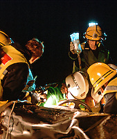 Firefighter holding a drip for a doctor who is operating upon a trapped driver in a crashed car following a road traffic accident...© SHOUT. THIS PICTURE MUST ONLY BE USED TO ILLUSTRATE THE EMERGENCY SERVICES IN A POSITIVE MANNER. CONTACT JOHN CALLAN. Exact date unknown.john@shoutpictures.com.www.shoutpictures.com..
