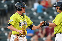 Right fielder Ian Strom (40) of the Columbia Fireflies is greeted after scoring a run in a game against the Rome Braves on Sunday, August 20, 2017, at Spirit Communications Park in Columbia, South Carolina. Rome won, 11-6 in 16 innings. (Tom Priddy/Four Seam Images)