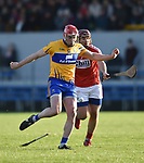 Niall Deasy of Clare scores a point despite Cork's Richard Cahalane during their Munster Hurling League game at Cusack Park. Photograph by John Kelly.
