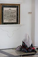 Muslim Woman Reading at the Ubudiah Mosque, Kuala Kangsar, Malaysia.