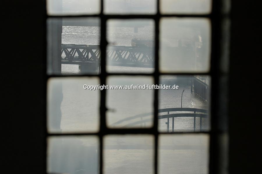 4415/Fensterbild:DEUTSCHLAND, HAMBURG, 09.02.2004: Speicherstadt, Blick aus dem Speicherfenster Block V auf den Magdeburger Hafen mit der Magdeburger Bruecke und hinten Baackenbruecke Die Speicherstadt in Hamburg ist der groesste, auf Eichenpfaehlen gegruendete Lagerhauskomplex der Welt und steht seit 1991 unter Denkmalschutz...Zum Baubeginn der etwa 1,5 Kilometer langen Speicherstadt im Freihafen wurden ab 1883 die Haeuser auf den Elbinseln Kehrwieder, Brook und Wandrahm abgerissen und ca. 20.000 Menschen mussten neue Wohnungen finden. Notwendig wurde der Bau durch den Anschluss Hamburgs an den Deutschen Zollverein im Jahre 1888. Bis zu diesem Zeitpunkt war ganz Hamburg Zollausschlussgebiet. Um den Hafenbetrieb nicht durch Zoelle zu stoeren, wurde der Bau eines Viertels noetig, das nicht zum deutschen Zollgebiet gehoerte, sondern Freihafengebiet war. Dadurch konnte der Ueberseehandel zollfrei abgewickelt werden - diesen besonderen Status als zollfreies Gebiet hatte die Speicherstadt bis 2004...Die Lagerhaeuser (Speicher) in neugotischer Backsteinarchitektur haben jeweils auf der einen Seite Anbindung ans Wasser (Fleet) und auf der anderen Seite an die Straße. Gelagert wurde Stueckgut, vor allem Kaffee, Tee und Gewuerze. In den Lagerhaeusern, die meistens unbeheizt waren und Holzfußboeden hatten, herrschten relativ gleichmaeßige klimatische Lagerbedingungen.