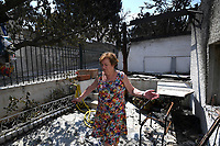 Pictured: A local home owner stands in disbelief in what used to be her house in the aftermath of the forest fire which has claimed dozens of lives in the Mati area of Rafina, Greece. Wednesday 25 July 2018<br /> Re: Deaths caused by wild forest fires throughout Greece.