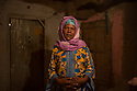 Morocco - Ouarzazate - Kasbah Taourirt - Kabira Oufakkir, 37, stands in front of the room she rents.A destitute mother of two, Kabira Oufakkir has been living in the Kasbah Taourirt for the past 16 years, renting a modest room she shares with her two sons. A maid and cleaning lady, thanks to her dark skin Oufakkir has participated in several historical and biblical movies, such as Abraham, Moses and Isaiah, generally acting as a slave. She recently featured in a Moroccan movie, acting as an African migrant crossing the Sahara in order to reach Europe.
