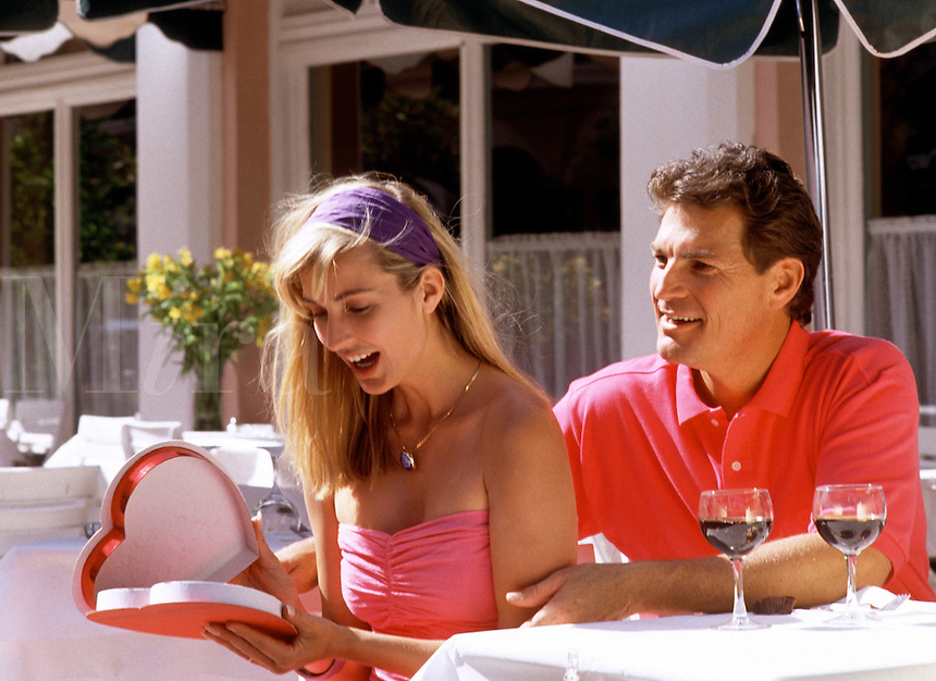 A romantic couple at an outdoor cafe; the woman has a surprised expression as she opens a box of Valentine's Day chocolates.