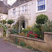 The exterior of a stone cottage with a wrought-iron gate and railings. Two trained fruit trees stand in the front garden.