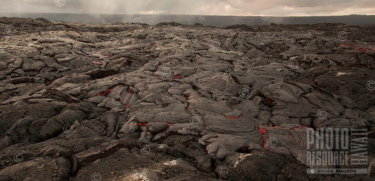Lava surface flow slowly moves along a coastal plain, creating new land between Kalapana and Hawai'i Volcanoes National Park, Big Island.