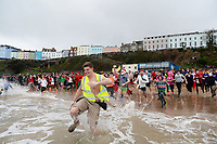 Pictured: People take to the water. Tuesday 26 December 2017<br /> Re: Hundreds took part in this year's Tenby Boxing Day Swim which sees people in fancy dress taking to the sea in Tenby, west Wales, UK.