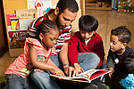 Education Preschool Headstart young male teacher reading to group of two boys and a girl