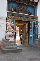 Kathmandu, Nepal.  Entrance to the Hanuman Dhoka, a Former Royal Palace, Durbar Square.  A stone lion, ridden by Parvati, wife of Shiva, guards the left side of the entrance.  A more modern guard, a soldier, stands in the doorway.