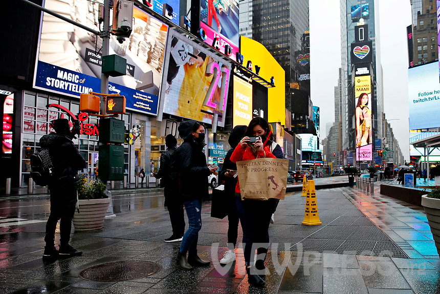 NEW YORK - NEW YORK - MARCH 24: A woman takes pictures at Times Square on March 24, 2021 in New York. With more people every day getting vaccinated transmission rates are dropping, arts an entertainment values should open at 33% capacity on April 2, as outdoor amusement parks will open at 25% capacity one week later (Photo by John Smith/VIEWpress)