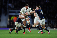 Courtney Lawes of England is tackled by Dougie Fife of Scotland