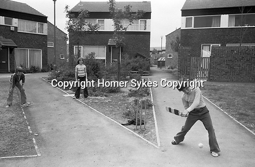 1970s England kids playing cricket outside in a traffic free pedestrian walkways. Boys and a girl  who live in this recently built modern housing development its a new town 1977 UK Milton Keynes Buckinghamshire.