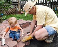 Little Boy helping dad laying stone