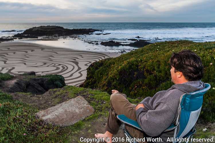 Sand artist, Jesse Meyer, sits back and appreciates his work.
