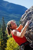 Female climber climbing overhanging rock face, Banff, Banff National Park, Alberta, Canada