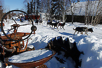 Robert Nelson Jr. passes by an old tractor as her runs down the street at the Shageluk village checkpoint during the 2011 Iditarod race..