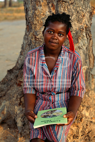 """Mbati, Zambia. Woman student in uniform holding a booklet called """"Zambia's Pride"""", sitting at the foot of a tree."""