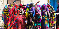Colorful group of Indian women having fun and throwing color powder, during the Holi celebration in Mathura Uttar Pradesh, India