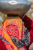 Abhaneri, Rajasthan, India.  Pot of Water Rests on a Fiber Pad on top of the Head of a Village Woman.