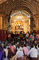 Myanmar, Burma.  Mandalay.  Mahamuni Buddhist Temple.  Buddha covered in gold leaf.  Only males are allowed to approach the Mahamuni Buddha.