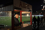 Ashton United 6 Ramsbottom United 0, 12/01/2016. Hurst Cross stadium, Northern Premier League. The club's lottery seller in his stand before the fixture between Ashton United and Ramsbottom United in the Northern Premier League premier division. The match was played at Ashton's Hurst Cross stadium, the club's ground. The club was originally founded in 1878 as Hurst F.C. and by 1880 the club were playing at Hurst Cross, their current ground which makes their home one of the oldest football grounds in the world. Ashton won the match 6-0, watched by a crowd of 178. Photo by Colin McPherson.