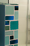 Blue and green recycled glass tiles offer an eye-catching contrast to the white tiles in this newly-remodeled bathroom.