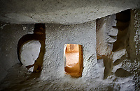 Pictures & images of cave room with a defensive entrance , Aynali Kilise cave church, 11th century, near Goreme, Cappadocia, Nevsehir, Turkey<br /> <br /> It can be seen that the inner room is enterd via a very small tunnel. The tunnel has a groove cut into it and the round rock rolls into this sealing the tunnel and stopping any attackers from entering the inner room. Stairs can be seen to the right of the door leading up to the upper gallery rooms of the monastery.