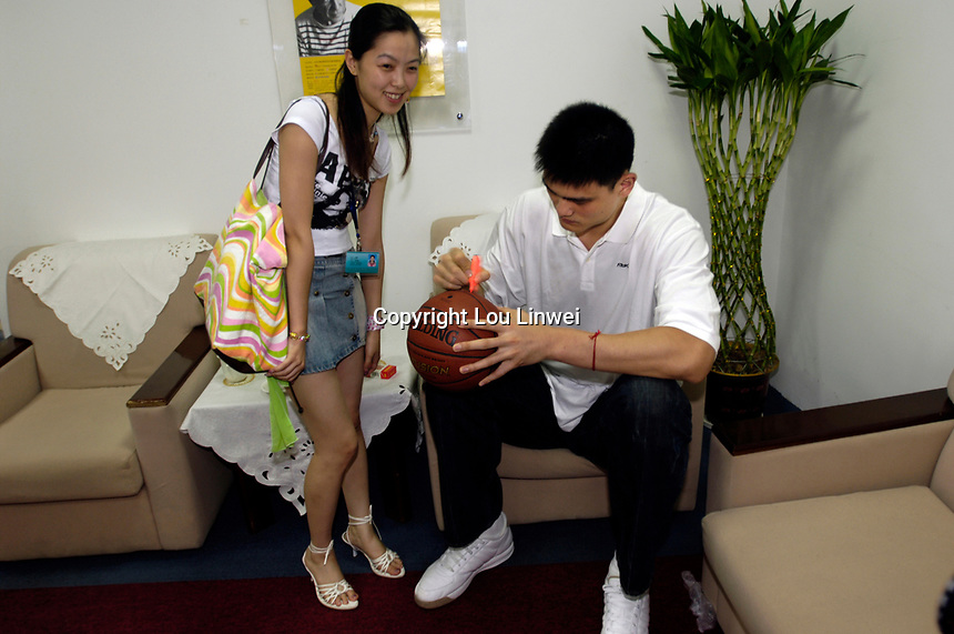 NBA Houston Rockets player Yao Ming autographs a basketball for a lady before a press conference for the 2007 Special Olympics in Beijing, China.  July 21, 2006. (photo by Lou Linwei/Sinopix)