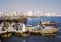 Dubai 1972, United Arab Emirates.  Abras (Water taxis) Crossing The Creek.  National Bank of Dubai in center;  Apartment and Office Buildings in the Background.