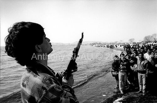 Durres, Albania<br /> February 1997<br /> <br /> Mafia gunmen control the entrance to a pier where a small ship was to take Albanians paying from $250 to $500 to a larger ship, which will go to Italy. The gunmen fired wildly into the air & screamed at the crowds to stay back.