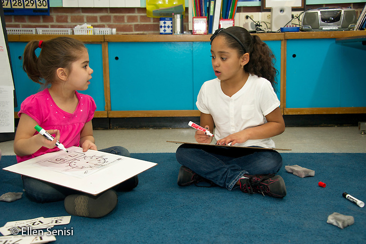 MR / Schenectady, New York. Paige Elementary School (urban public elementary school). First grade independent work at learning center time. Students (girls: 7) work together on time telling using dry erase boards. MR: Dei1, Liv3. ID: AL-g1g. © Ellen B. Senisi.