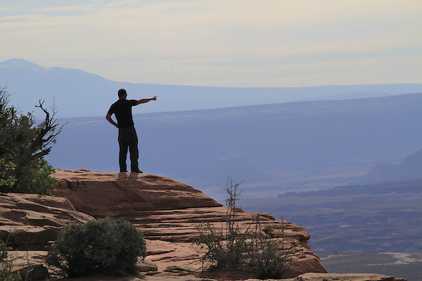 Man pointing the way at Grand View Point Overlook in Canyonlands National Park, Utah, USA. .  John offers private photo tours in  Canyonlands National Park and throughout Utah and Colorado. Year-round.