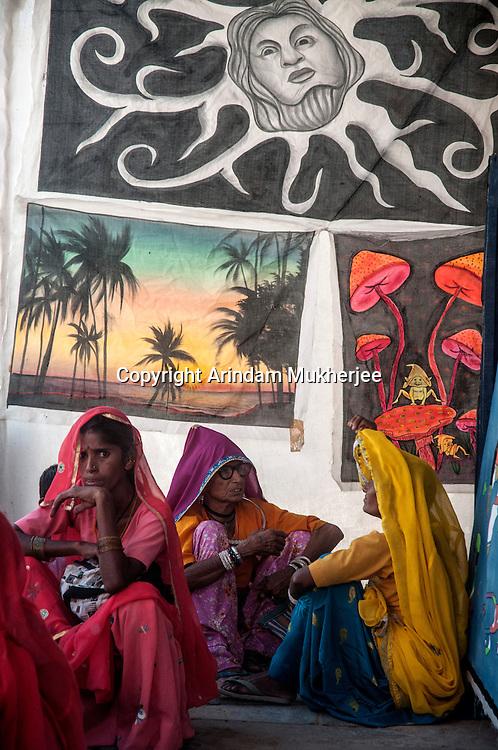 Ladies sitting in front of Wall hangings at Pushkar fair. Rajasthan, India.