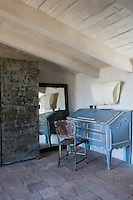 A corner of a rustic bedroom with terracotta floor tiles and painted beamed ceiling. The room is simply furnished with a steel cupboard, a blue painted Baroque bureau and an iron chair