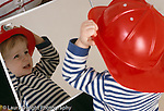 18 month old toddler boy looking at self in mirror wearing toy fire hat horizontal recognizing self