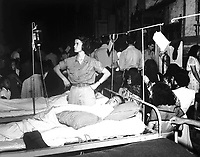 1st Lt. Phyllis Hocking adjusts glucose injection apparatus for a GI patient in the 36th Evac. Hospital, Palo, Leyte, P.I., quartered in the Church of the Transfiguration, as the congregation kneels during Christmas Eve services.  December 24, 1944.  (Army Staff)<br /> NARA FILE #:  319-CE-124-237580<br /> WAR & CONFLICT BOOK #:  922