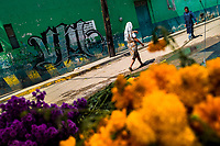 A Mexican woman walks in front of piles of marigold flowers (Flor de muertos) during the Day of the Dead celebrations in Oaxaca, Mexico, 30 October 2019. Day of the Dead (Día de Muertos), a religious holiday combining the death veneration rituals of Pre-Hispanic cultures with the Catholic practice, is widely celebrated throughout all of Mexico. Based on the belief that the souls of the departed may come back to this world on that day, people gather together while either praying or joyfully eating, drinking, and playing music, to remember friends or family members who have died and to support their souls on the spiritual journey.