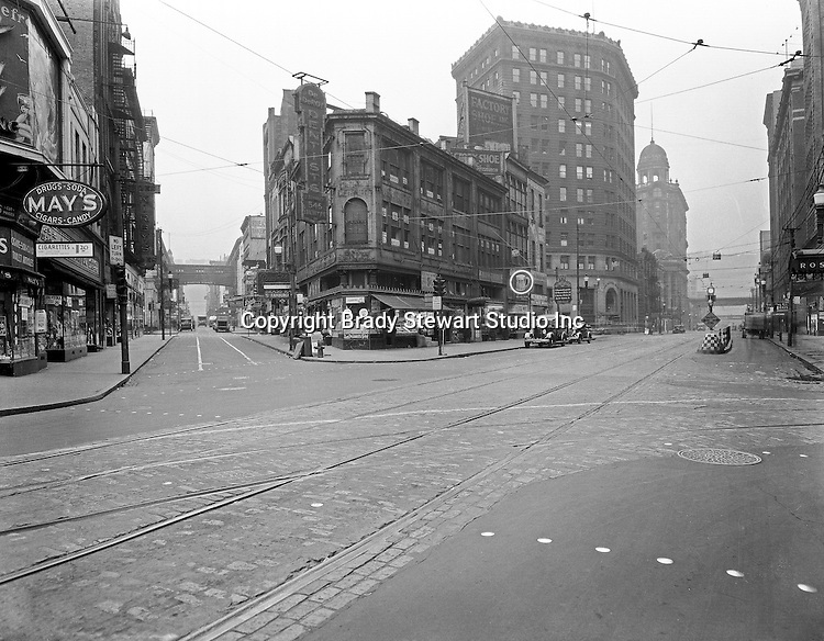 Pittsburgh PA:  View down Liberty Avenue (right) and Market Street (left).  Nearby stores include drug store chain May's, Brass Rail, Weinberger's Discount Drug Store, Dr. Deroy Dentist
